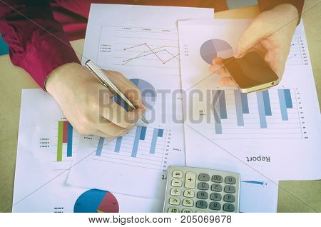 top view of working hand writing and using smart phone with business strategy diagram report and calculator on desk at home office income and expenses finance searching data and economy concept