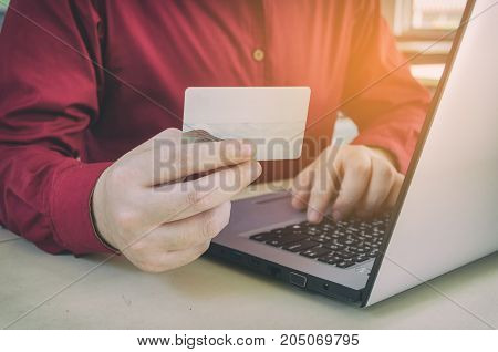 close up hand paying with credit card and typing on laptop computer on desk at home office payment and shopping online income and expenses searching data social network and check email concept