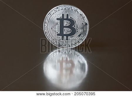 The silver coin bitcoin lies or stands on the edge on a dark mirror background reflected. The concept of crypto currencies.