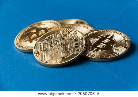 A few gold and silver coins bitcoin lie on a blue backgroundConcept of crypto currency