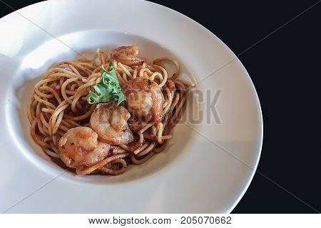 Fresh homemade traditional Italian popular and authentic cuisine Spaghetti serve in white plate on black background.