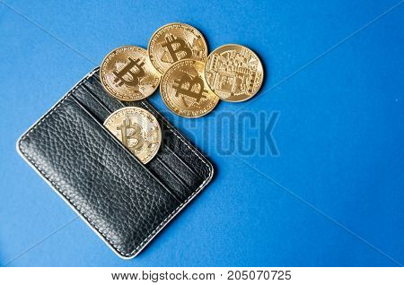 Black leather wallet on a blue background with several gold coins of bitcoins falling out of their pockets. The concept of crypto currencies.
