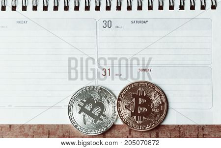Two bitcoins are lie on the planing. On the calendar are the last days of December 2017. The concept of crypto currencies.