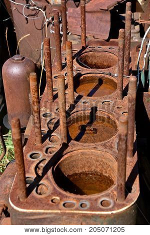 Water has accumulated in the cylinder block of an old rusty tractor four cylinder engine