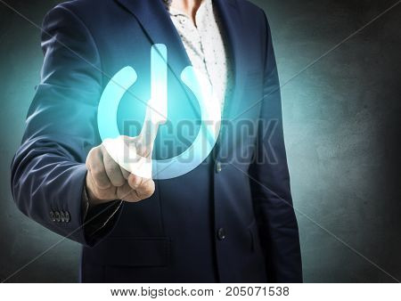 Businessman pressing power button over gray wall background.