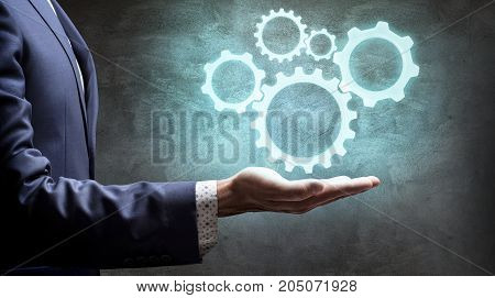 Businessman pressing on group of digital cogwheels. Harmonious work concept.