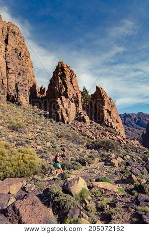 Trail running girl in mountains on rocky path. Cross country runner training in inspiring nature dirt footpath on Tenerife Canary Islands Spain.