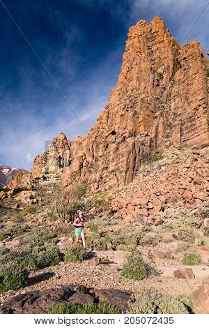 Young woman running in mountains on rocky trail. Cross country runner training in inspiring nature rocky footpath on Tenerife Canary Islands Spain.