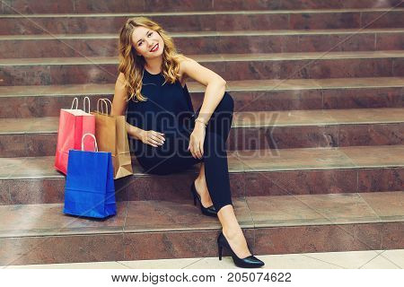 Beautiful young woman sit on stairs during shopping with shopping bags in store.