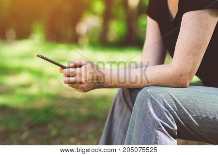 Woman using smartphone in public park female hands typing sms text message