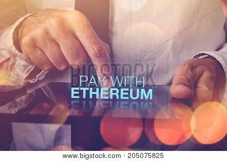 Pay with Ethereum cryptocurrency concept with businessman and digital tablet