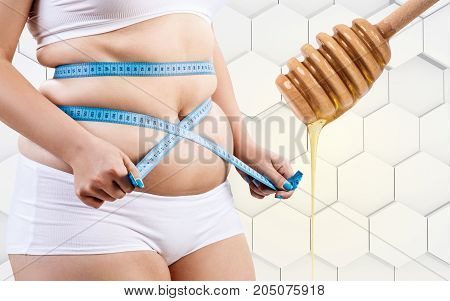 Fat woman and spoon with honey preparing for massage. Honey massage concept.