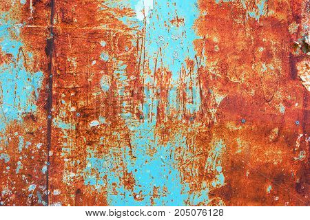 Teal and orange toned grunge corroded rusty metal plate surface texture as background