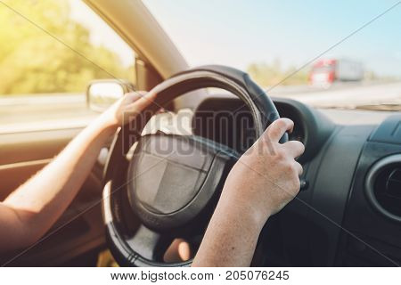 Female hands holding on black steering wheel and driving car on motorway on sunny summer day