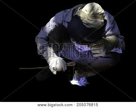 Posture of Worker man in personal protective equipment welding by transformer welding machine in black background.