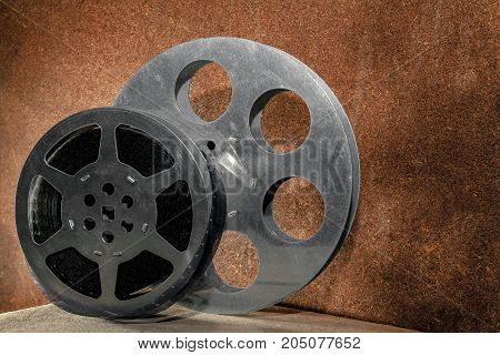 Two reels with a film on a wooden background