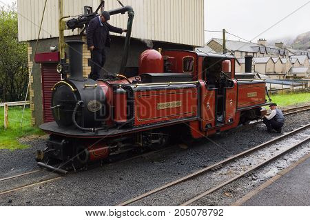 Blaenau Ffestiniog Wales UK - September 4 2017: Narrow gauge steam locomotive David Lloyd George of the Ffestiniog Railway Company having her water tanks filled at the station