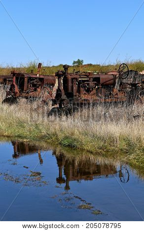 Reflections of several old tractors in a salvage and junkyard are reflected in a pool of water.