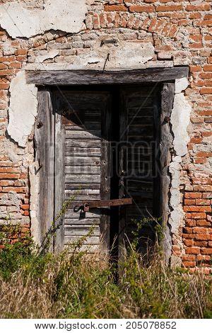 Broken wooden entrance door of an old brick house