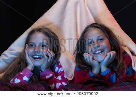 Kids wearing red jammies in bed on black background. Girl friends watching TV in blanket tent. Pyjamas party for children. Girls with happy faces. Children and fun time concept.