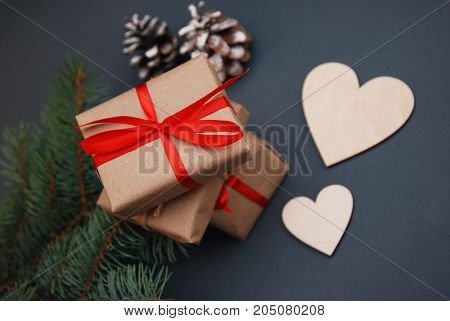 Christmas gift box. Christmas presents in red boxes at black wooden table. Flat lay with copy space.