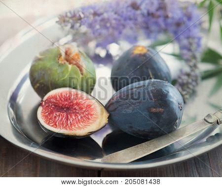Whole and sliced figs on a plate and on a wooden table. Beautiful still life.Focus is on the sliced fig.