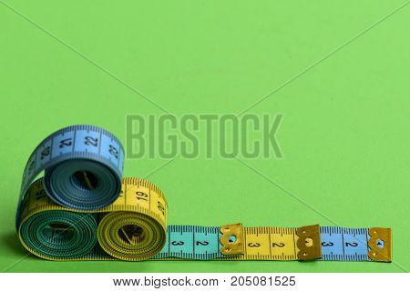Tape Measures Of Cyan, Blue, Yellow Colors Placed In Pyramid
