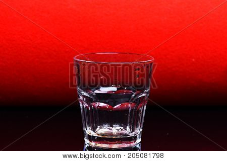 glass for whiskey with water drops on red and black background copy space