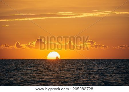 Albania. Golem. Sunset on the Adriatic Sea with the silhouette of the ship on the horizon