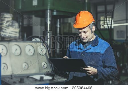Working In The Plant With Tablet In Hands On The Background Of The Equipment