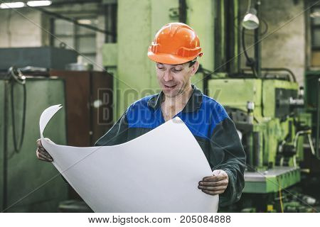 Working in production against a background of machines from the engineering drawings in his hands while working