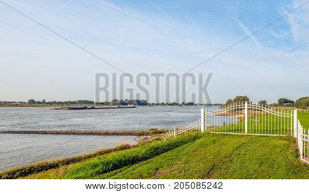 White iron gate next to a wide Dutch river with a large cargo ship loaded with coal sailing upstream. It is early in the morning of a sunny day in the late summer season.