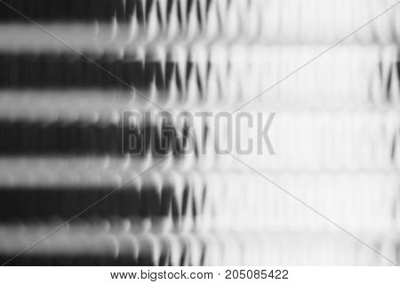 Blurred metal surface. Steel texture. Transparent fluted glass.