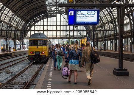 AMSTERDAM NETHERLANDS - JUL 27 2012: Passengers enter a regional train at Amsterdam Central Station.