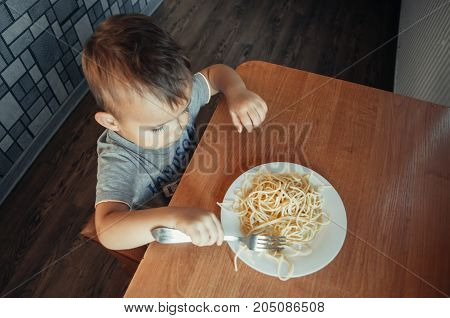The Child At The Table Eating Macaroni And Interesting Angle