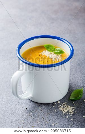 Delicious homemade carrot soup with meat sesame seeds in enamel mug. Healthy food concept with copy space.