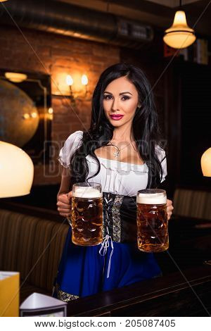 Young waitress brings beer to visitors. Oktoberfest. Sexy woman in dirndl dress holding Oktoberfest beer stein.