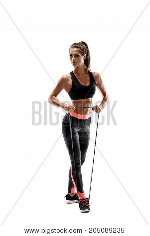 One caucasian woman exercising fitness resistance bands in studio silhouette isolated on white background