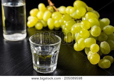 Glasses and bottle of traditional drink Ouzo or Raki on black dish with a branch of grapes