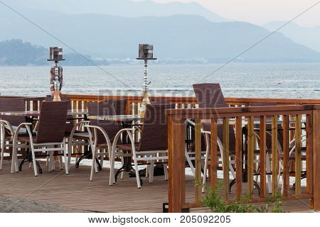 The tables of the cafe with beautiful views of the sea and the mountains in Kemer, Turkey. Palm trees and lanterns