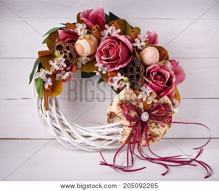 Handmade wreath. Wicker Wreath. Interior decoration. The wreath is decorated with flowers and quail eggs