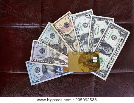 The concept of storing and accumulating money - a credit bank card rests on a set of dollars on the background of a leather chair
