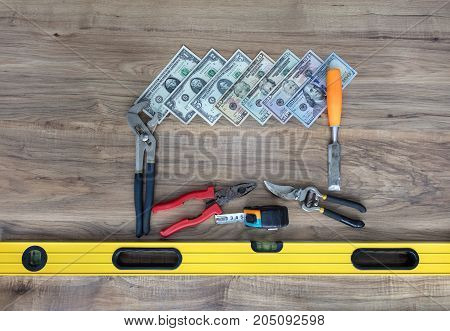 Old construction tools adjustable spanner chisel nippers level tape measure and dollars are located on a wooden table close-up
