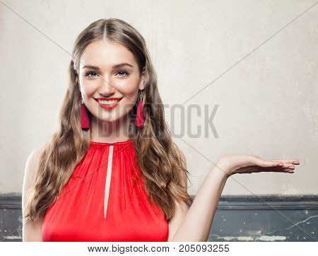 Happy Smiling Woman Showing Empty Copy Space on the Open Hand. Empty Hand Fashion Makeup Long Hair and Red Earrings