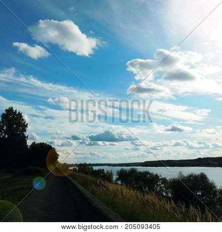 Blue sky with cumulus and feather clouds illuminated by the sun rays