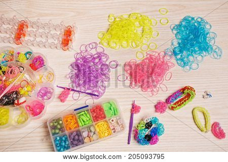 colored elastics and devices for weaving of rubber band bracelet on wooden background