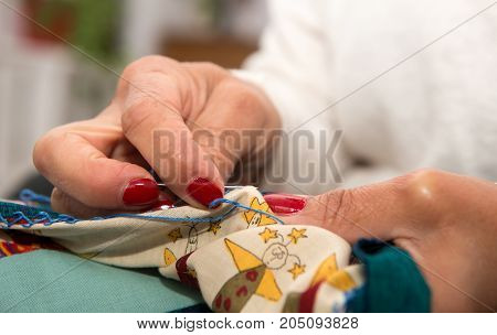 seamstress woman hands sewing for finish a quilt.