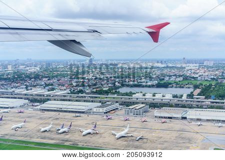 Scenery from airplane 's window after taking off seeing wing of airplane and landscape of Bangkok and airport
