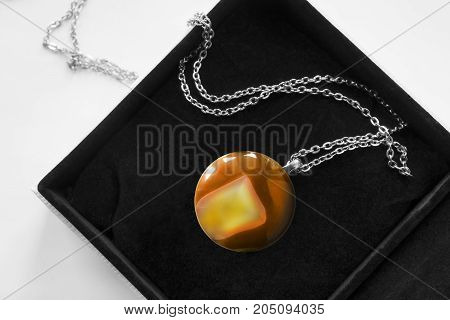 Large amber pendant in black jewel box closeup