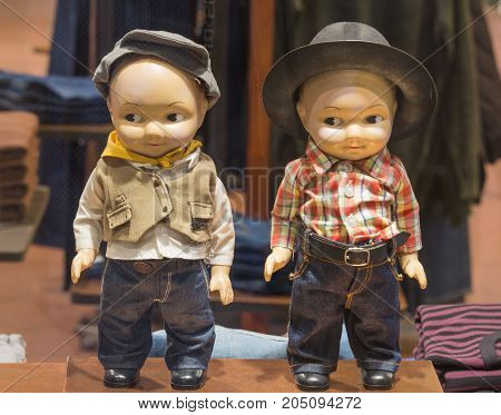 Two children mannequins dressed. No brand names or copyright objects. Baby dummy dolls in a shop window in St. Petersburg, Russia. Hat, shirt, jeans for kids.